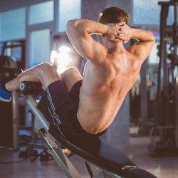 Young fitness man doing incline sit-up exersises