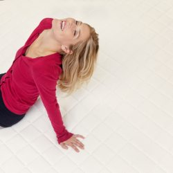 Happy woman relaxing on mattress with head back in furniture store