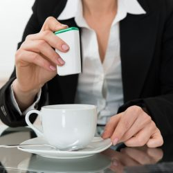 Close-up Of Young Businesswoman Putting Sugar In Cup At Glass Desk