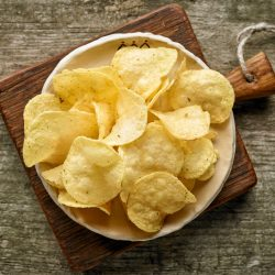 potato chips on wooden table, top view