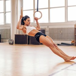 Young fit woman doing pull-ups on gymnastic rings. Muscular young female athlete exercising with rings at gym.