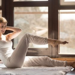 Young smiling attractive woman doing rock press exercise, crisscross, leg raising and twisting pose with hands behind head, sit ups, working out, wearing white sportswear, full length, home interior
