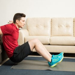 Man doing tricep dips using a couch at home